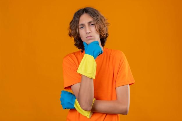 黄色の背景に物思いに沈んだ表情でカメラを見てあごに手で立っているゴム手袋を着用してオレンジ色のtシャツの若い男