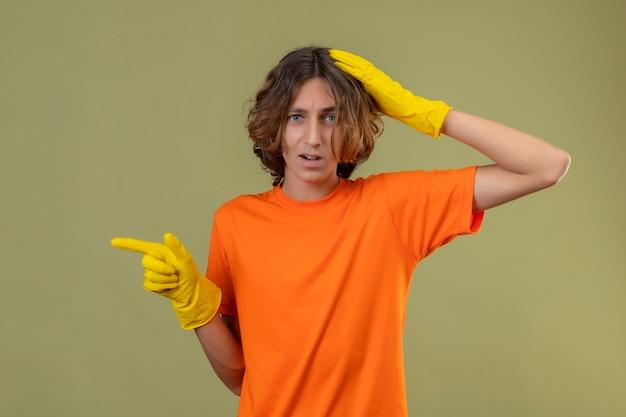 緑の背景で混乱している指で側を指している間違いのための頭の上に手で立っているゴム手袋を着用してオレンジ色のtシャツの若い男