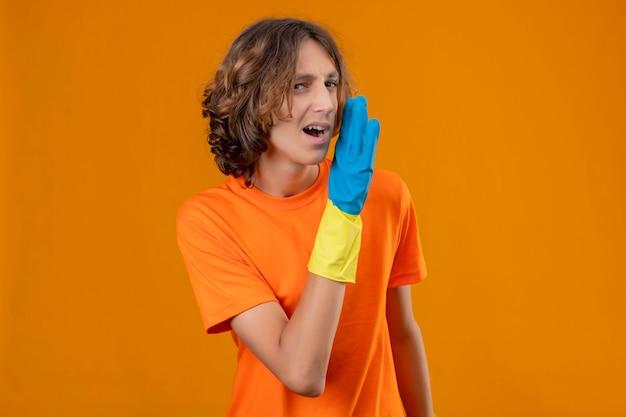 黄色の背景の上に立って自信を持って探している口の近くの手で秘密を告げるゴム手袋を着用してオレンジ色のtシャツの若い男