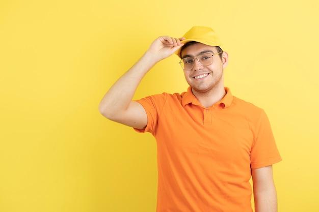 オレンジ色の制服を着た若い男が立ってポーズをとる。