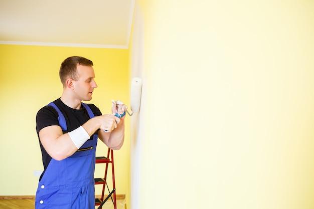 オーバーオールの若い男はペイントローラーを持っています。アパートの部屋の改修のためのツールアクセサリー。リノベーションのコンセプト