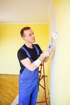 작업복을 입은 청년이 페인트 롤러를 들고 있습니다. 아파트 룸 리노베이션을 위한 도구 액세서리. 홈 리노베이션 개념