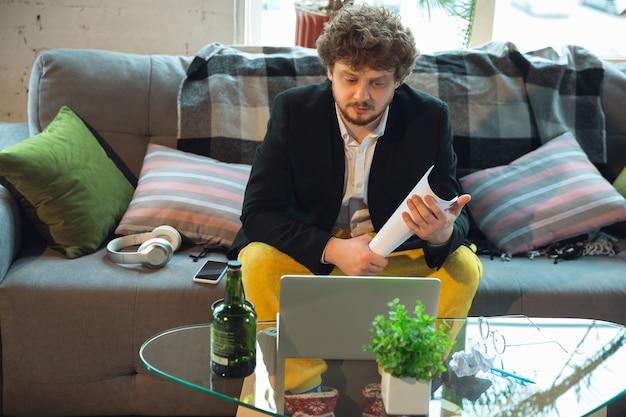 Молодой человек в пижаме и куртке, работая на удаленном офисе ноутбука во время коронавируса, весело и