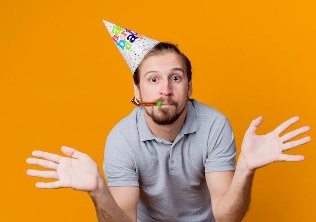 オレンジ色の壁の上に立っている誕生日パーティーのコンセプトの側面に幸せで驚きの腕を広げて笛を吹くパーティーキャップの若い男