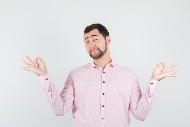 Молодой человек в розовой рубашке делает медитацию с закрытыми глазами и выглядит расслабленным