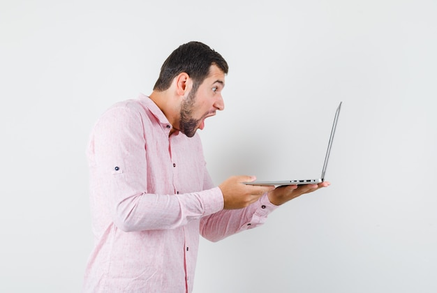 Молодой человек в розовой рубашке смотрит на портативный компьютер и выглядит шокированным