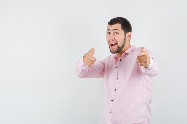 カメラを指して楽観的に見えるピンクのシャツを着た若い男