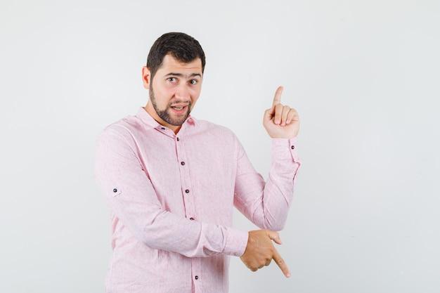 ピンクのシャツを着た若い男が上下を指して楽観的に見える