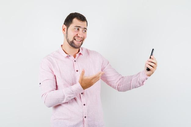 Молодой человек в розовой рубашке позирует, держа мобильный телефон и выглядит веселым