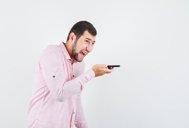 음성 메시지를 녹음하고 분노하는 동안 소리 치는 분홍색 셔츠에 젊은 남자