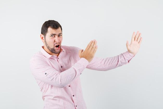 Молодой человек в розовой рубашке показывает жест каратэ и выглядит сердитым