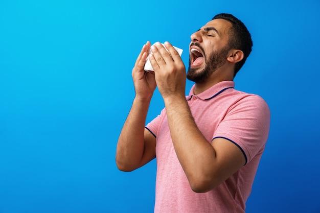Молодой человек в розовой рубашке с аллергией или простудой сморкается тканью на синем фоне
