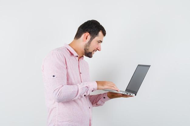 Молодой человек в розовой рубашке работает с портативным компьютером и выглядит занятым