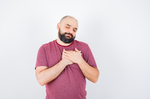 ピンクのtシャツを着た若い男が胸に手を握り、希望に満ちた正面図を探しています。 無料写真