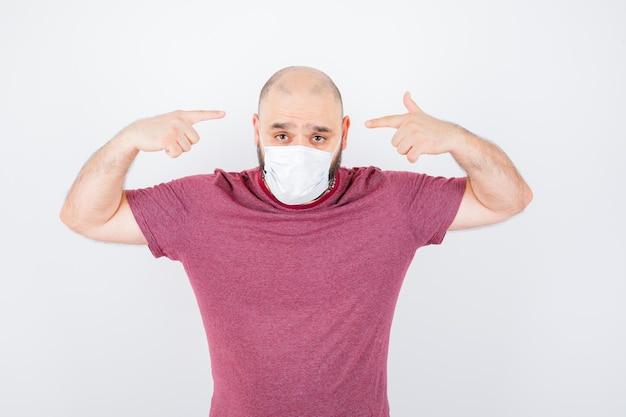 분홍색 티셔츠를 입은 청년, 그의 머리를 가리키는 마스크, 전면 전망.
