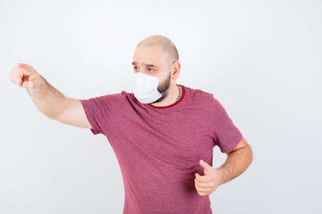 분홍색 티셔츠를 입은 청년, 앞을 가리키고 집중된 앞모습을 바라보는 마스크.