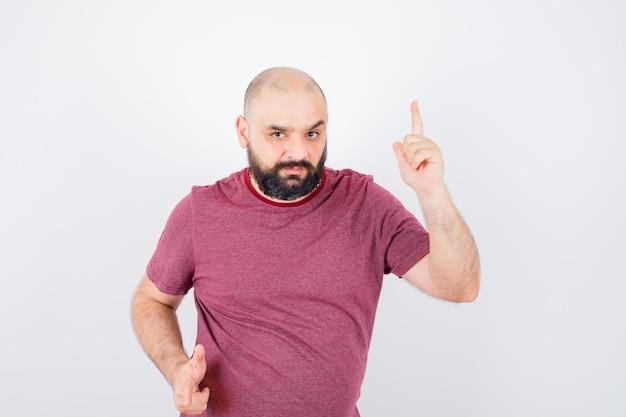 분홍색 티셔츠를 입은 젊은 남자가 위를 가리키고 초점이 맞춰져 있는 앞모습을 보고 있습니다.