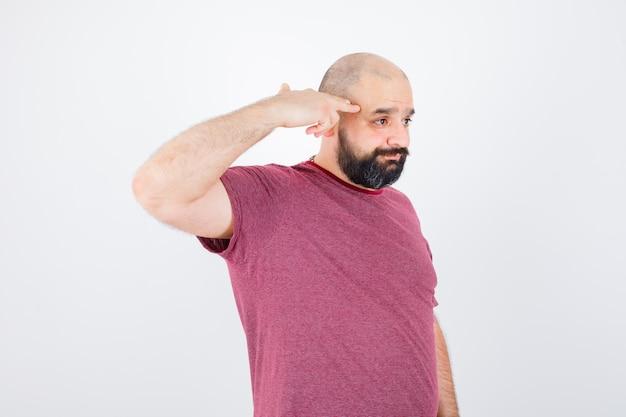 Молодой человек в розовой футболке показывает жест пистолета и выглядит мрачно, вид спереди.