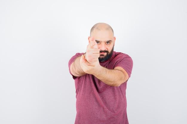 권총 제스처, 전면 보기를 보여주는 분홍색 티셔츠에 젊은 남자.
