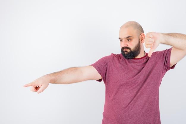 ピンクのtシャツを着た若い男が、正面を向いて緊張しているときに親指を下に向けています。