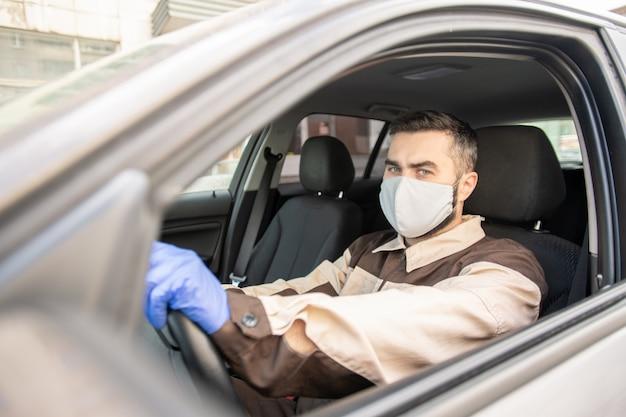 車に座ってクライアントにオンライン注文を配信するために運転している保護手袋、マスク、作業服の若い男