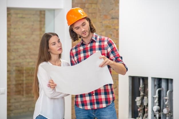Молодой человек в защитном шлеме и клиентка изучают дизайн проекта
