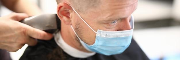 顔の保護マスクの若い男は、美容院の肖像画で散髪をします。 covid19流行の概念の間の美容院でのサービス。