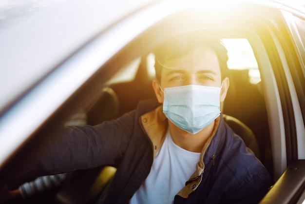 보호용 멸균 의료 마스크를 쓴 젊은 남자가 차를 몰고 있습니다. 코로나 19.