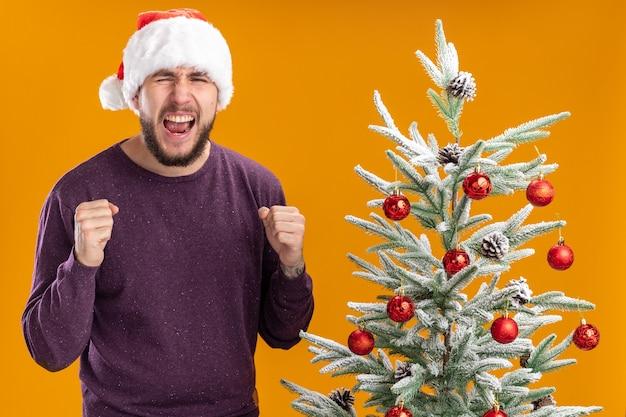 オレンジ色の背景の上のクリスマスツリーの横に立っている積極的な表情で叫んで拳を握り締める紫色のセーターとサンタ帽子の若い男