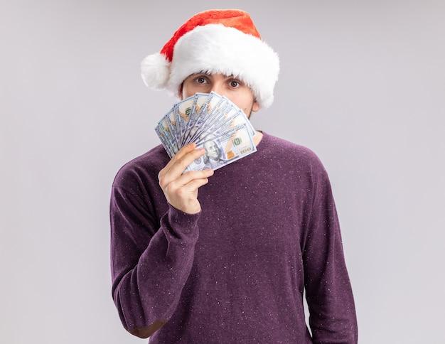 白い背景の上に立っている深刻な顔でカメラを見てお金で顔を覆う現金を保持している紫色のセーターとサンタ帽子の若い男