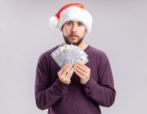 Молодой человек в фиолетовом свитере и шляпе санта-клауса держит деньги, глядя в камеру с серьезным лицом, стоящим на белом фоне