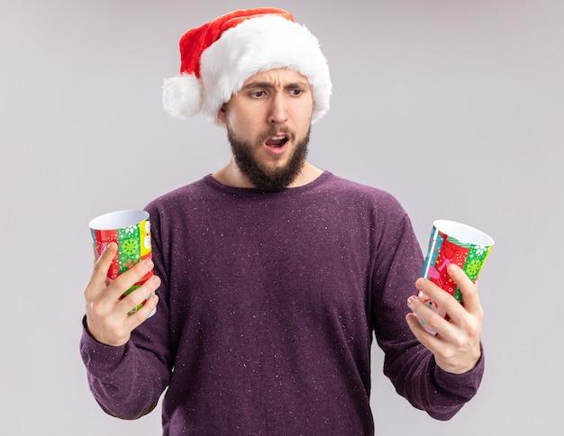 Молодой человек в фиолетовом свитере и шляпе санта-клауса держит красочные бумажные стаканчики, глядя на них в замешательстве и неуверенности, пытаясь сделать выбор, стоя на белом фоне