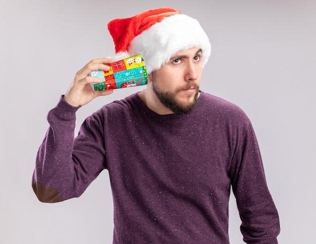 보라색 스웨터와 흰색 배경 위에 서있는 뭔가를 듣고 그의 귀에 다채로운 종이 컵을 들고 산타 모자에 젊은 남자