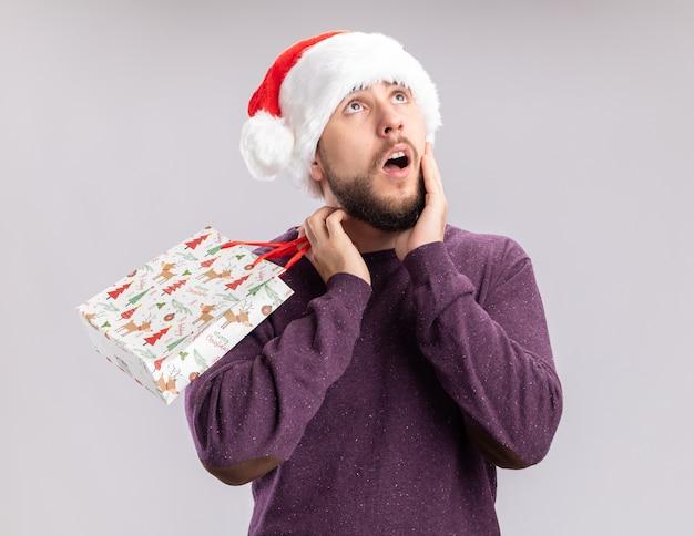 白い背景の上に立って困惑した見上げるギフト紙袋を保持している紫色のセーターとサンタ帽子の若い男