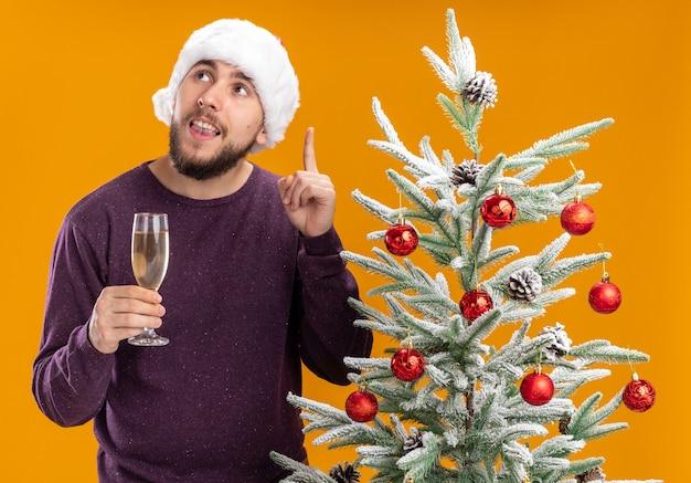 オレンジ色の背景の上のクリスマスツリーの横に立っている人差し指を示すスマートな顔に笑顔で見上げるシャンパンのガラスを保持している紫色のセーターとサンタ帽子の若い男