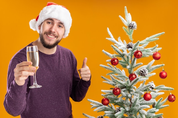 Молодой человек в фиолетовом свитере и шляпе санта-клауса держит бокал шампанского рядом с елкой на оранжевом фоне