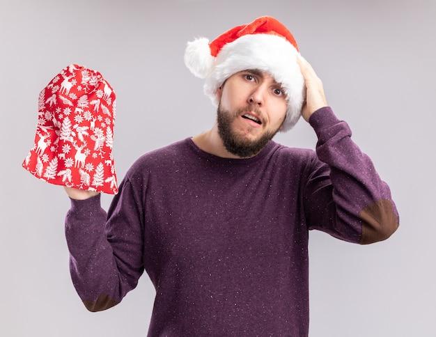 紫色のセーターとサンタの帽子をかぶった若い男が白い壁の上に立っている間違いのために彼の頭の手で混乱しているように見える贈り物と赤いバッグを持っています
