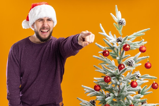 オレンジ色の背景の上のクリスマスツリーの横に立っている何かを人差し指で指しているイライラした表情で脇を見て紫色のセーターとサンタ帽子の若い男