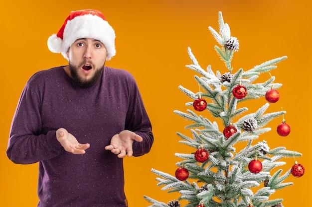 オレンジ色の背景の上のクリスマスツリーの横に立っている憤慨で育った腕と混同されたカメラを見て紫色のセーターとサンタ帽子の若い男