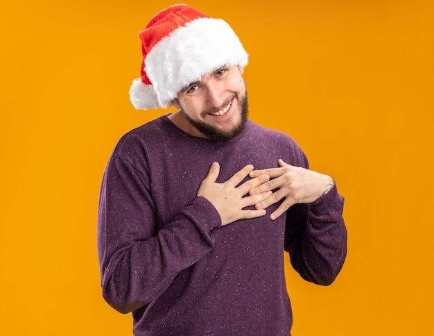 オレンジ色の背景の上に立って感謝を感じて胸に手をつないでカメラを見て紫色のセーターとサンタ帽子の若い男