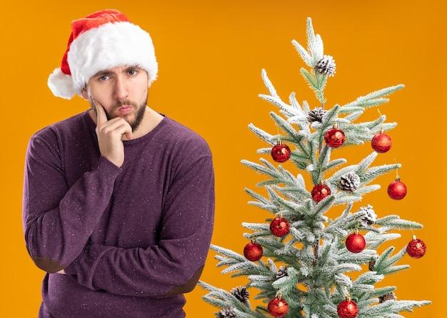 オレンジ色の背景の上のクリスマスツリーの横に物思いにふける表情でカメラを見て紫色のセーターとサンタ帽子の若い男