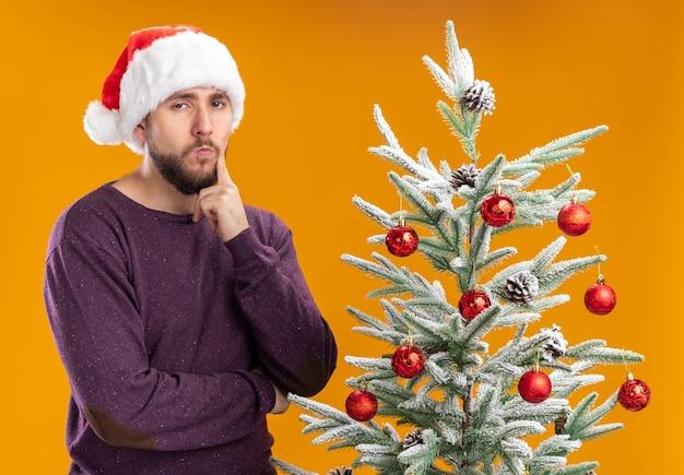 オレンジ色の背景の上のクリスマスツリーの横に立っている顔に懐疑的な表情でカメラを見て紫色のセーターとサンタ帽子の若い男