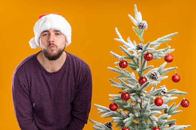Молодой человек в фиолетовом свитере и новогодней шапке выглядит уставшим и скучающим, стоя рядом с елкой на оранжевом фоне