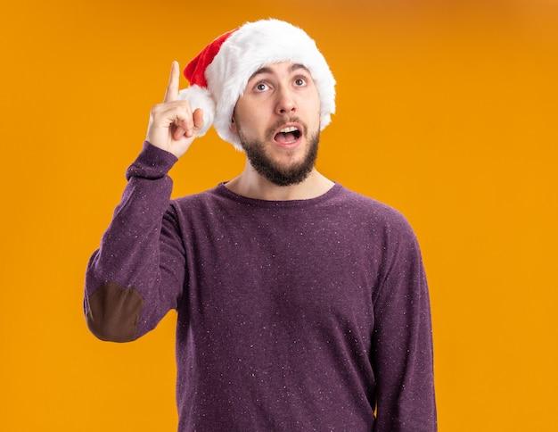 Молодой человек в фиолетовом свитере и шляпе санта-клауса смотрит вверх с удивлением, показывая указательный палец, имеющий новую отличную идею, стоящий над оранжевой стеной
