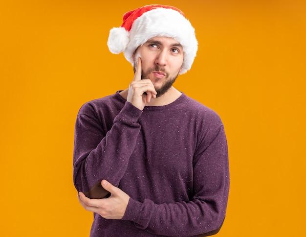 オレンジ色の背景の上に立って考える物思いにふける表情で彼の頬に指で見上げる紫色のセーターとサンタ帽子の若い男