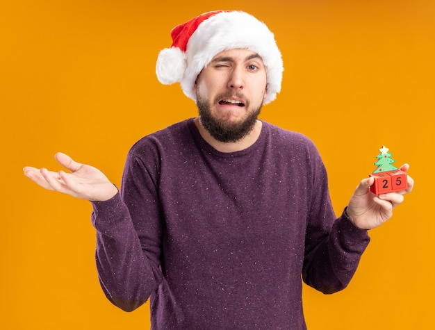 Молодой человек в фиолетовом свитере и новогодней шапке показывает игрушечные кубики с номером двадцать пять, смущенный и недовольный, пожимая плечами, стоит над оранжевой стеной
