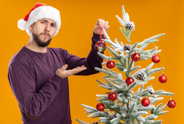 Молодой человек в фиолетовом свитере и шляпе санта-клауса стоит рядом с елкой и держит игрушку, висящую на дереве с серьезным лицом на оранжевом фоне
