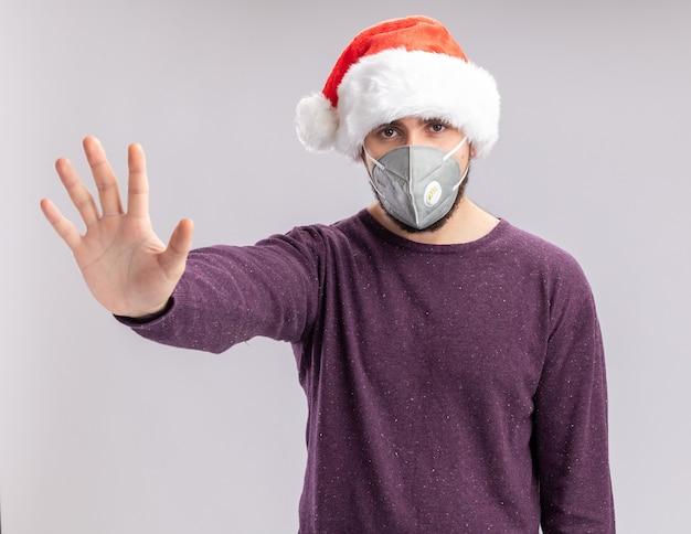 Молодой человек в фиолетовом свитере и шляпе санта-клауса в лицевой защитной маске смотрит в камеру с серьезным лицом, делая жест остановки с рукой, стоящей на белом фоне