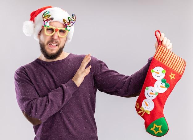Молодой человек в фиолетовом свитере и шляпе санта-клауса в забавных очках с рождественским чулком смущен, делая защитный жест руками, стоящими над белой стеной