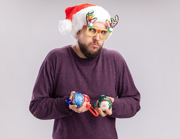 Молодой человек в фиолетовом свитере и шляпе санта-клауса в забавных очках держит елочные шары, глядя в камеру в замешательстве и неуверенно стоит на белом фоне